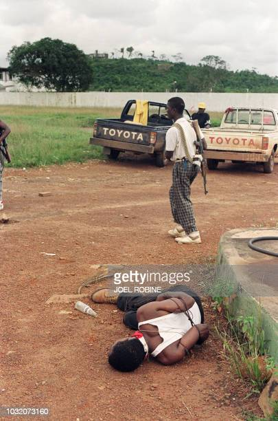 A government soldier loyal the warlord President Samuel K Doe made prisoner lies on the ground tied hands as a rebel soldier of the National...