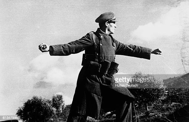 A government soldier prepares to throw a hand grenade towards enemy trenches during the Spanish Civil War June 3 1938