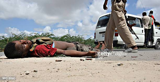 A government soldier walks past the body of a hardline Islamic fighter and used ammunition shells at KM4 XControl frontline section of Mogadishu...