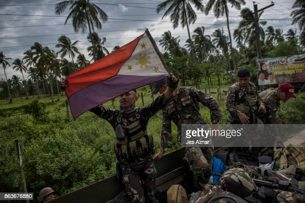 A government soldier waving the Philippine flag as they get ready to leave the battle against ISinspired militants on October 20 2017 in Saguiaran...