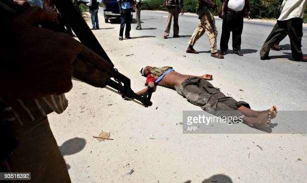 Government soldiers stand next to the body of a hardline Islamic fighter at KM4 XControl frontline section of Mogadishu where Islamist Fighters...