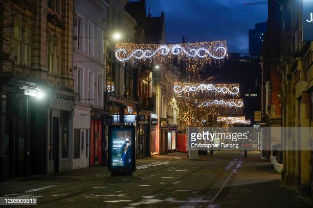 Government sponsored Covid-19 warning sign stands in the near deserted Manchester streets on December 31, 2020 in Manchester, England. New Year's Eve...