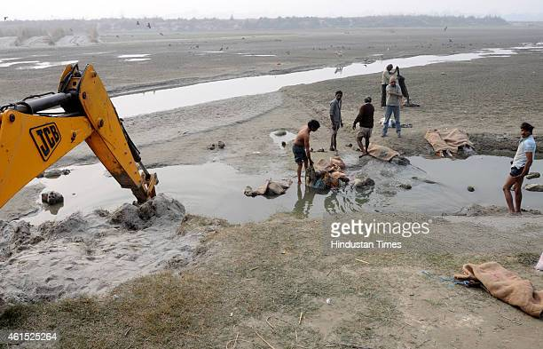 Government staff removing the dead human bodies that are found floating in Ganga river near Pariyar on January 14 2014 in Unnao India In a curious...