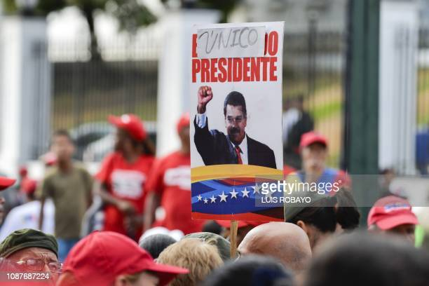 TOPSHOT A government supporter holds a sign reading The only president while listening to Venezuelan President Nicolas Maduro speaking at the...