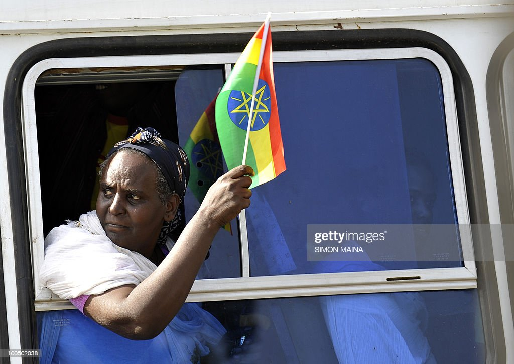 A government supporter of Ethiopian People's Revolutionary Democratic Front (EPRDF) waves a flag criticizing foreign rights groups from a bus window at the Meskel Square in Addis Ababa on May 25, 2010 as they celebrate their party's victory in the just concluded national election.The rally was organized as provisional returns showed a victory for the ruling Ethiopian People's Revolutionary Democratic Front and its allies.Sunday's vote had been closely watched by international observers after the contentious 2005 election, in which the opposition won a majority number of parliamentary seats only to endure police crackdowns and the killing of 193 demonstrators after the votes were counted.