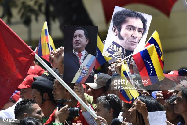 TOPSHOT Government supporters carry images of late Venezuelan President Hugo Chavez and Venezuelan Liberator Simon Bolivar during a rally in Caracas...