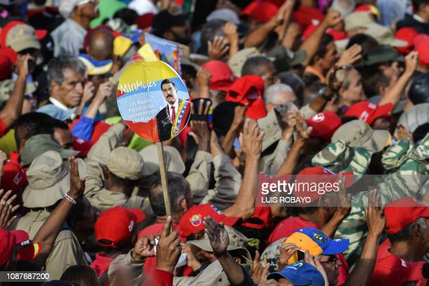 TOPSHOT Government supporters listen to Venezuelan President Nicolas Maduro speaking at the Miraflores Palace during a rally in which he announced...