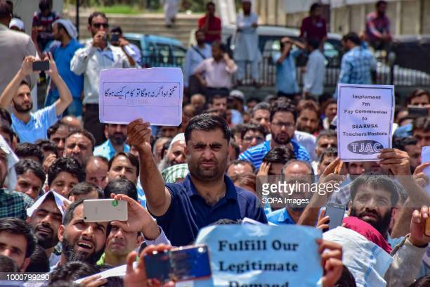 LAL CHOWK SRINAGAR JAMMU KASHMIR INDIA Government teacher holds placards during anti government protest in Srinagar on tuesday Police used water...