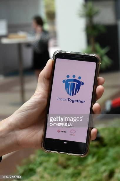 Government Technology Agency staff displays Singapore's new contacttracing smarthphone app called TraceTogether as a preventive measure against the...