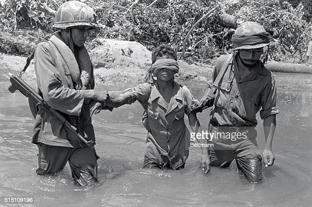 Government troops are seen here as they drag captive Khmer Rouge soldier across the stream following fire fight at Sala Lekpram 35 miles northeast of...