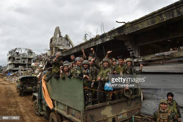 Government troops on board their trucks flash the victory sign as they prepare to leave the main battle area in Marawi on the southern island of...