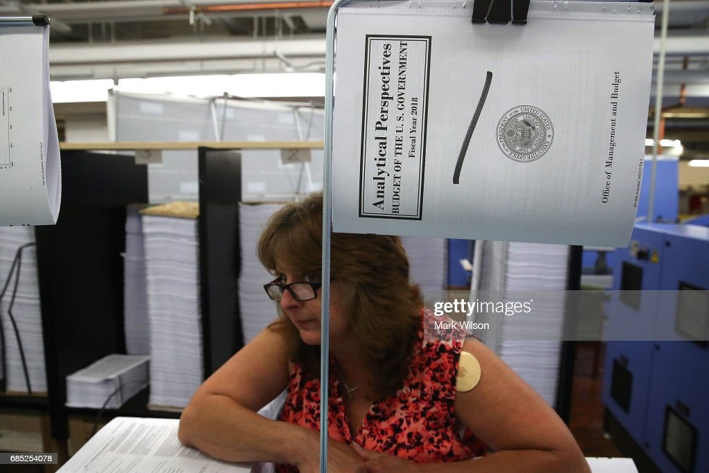 Government worker Laurie Ridgley watches as Office of Management and Budget Director Mick Mulvaney, tours the binding facility where President Trump's FY'18 budget books are being produced, at the Government Publishing Office, on May 19, 2017 in Washington, DC.