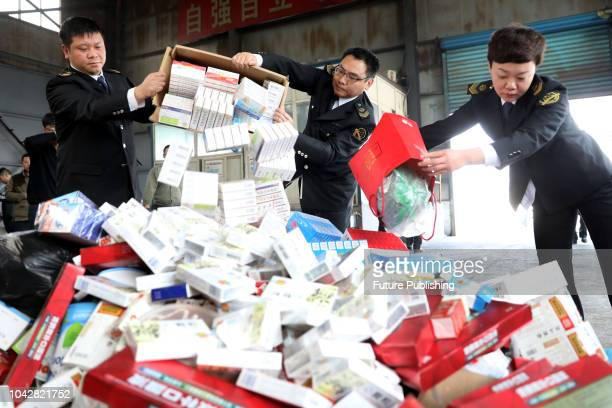 Government workers destroy confiscated medicines and food in Huaibei in central China's Anhui province Wednesday, March 14, 2018.PHOTOGRAPH BY...