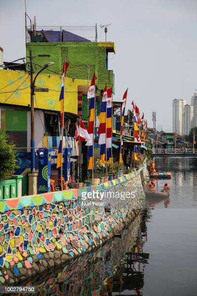 Government workers paint a wall of Sunter lake as part of a clean up campaign ahead of this year's Asian Games 2018 in Jakarta indonesia on Friday...