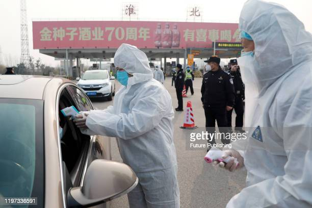 Government workers screen travelers in cars at a road checkpoint in Huaibei in central China's Anhui province Wednesday, Jan. 29, 2020.- PHOTOGRAPH...
