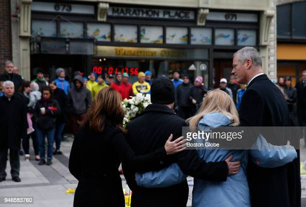 Governor Baker wraps his arm around Patricia Campbell mother of Krystle Campbell after laying a wreath at the site of one of the bombings in honor of...