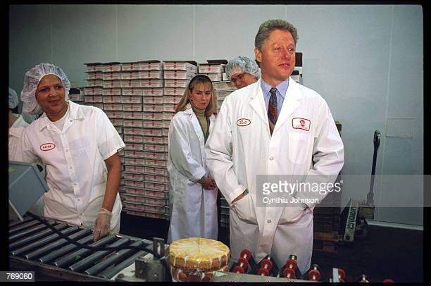 Governor Bill Clinton stands with his wife Hillary and workers in a cheesecake factory March 12 1992 in Chicago IL Clinton bested four other major...