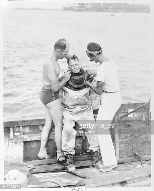 Governor Blanton Winship of Puerto Rico is helped into a standard Navy diving suit before descending 30 feet to the ocean bottom near here to explore...