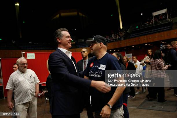 Governor Gavin Newsom and Richard Oliva, Reading Glasses volunteer, hug after Oliva thanked Newsom for his support of housing for the homeless while...