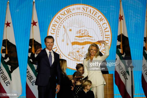 Governor Gavin Newsom and wife Jennifer Siebel Newsom gesture to the crowd after taking his oath of office on January 7 2019 in Sacramento California...