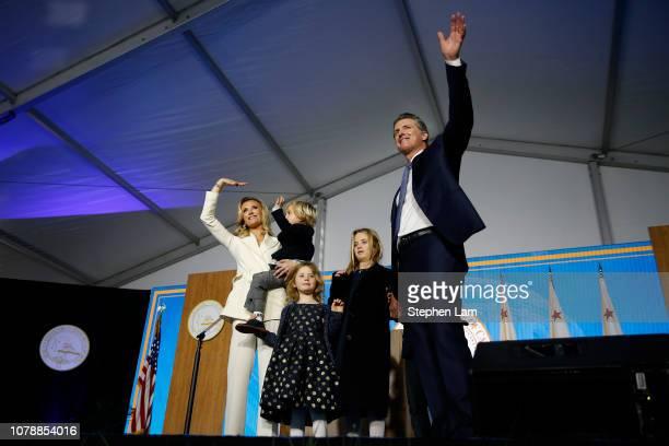 Governor Gavin Newsom gestures to the crowd alongside wife Jennifer Siebel Newsom and children Dutch Montana and Brooklynn on January 7 2019 in...