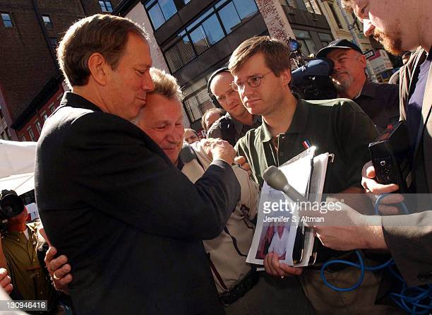 Governor George Pataki hugs Hans Gerhardt whose son Ralph Gerhardt and his friend Linda Luzzicone are missing near the Armory where families who have...