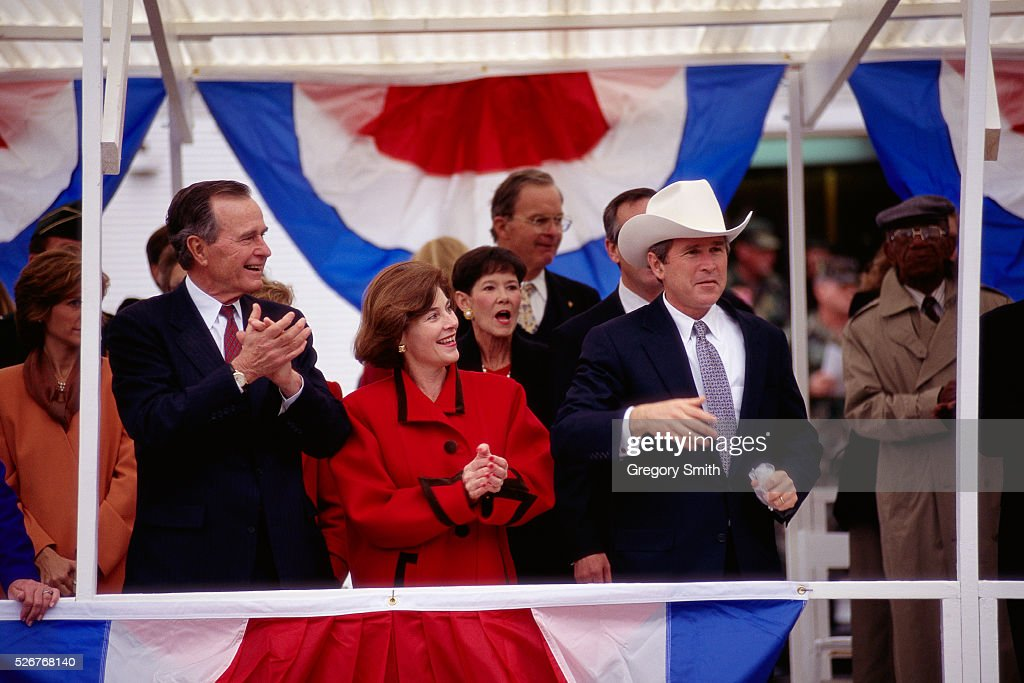 Governor George W. Bush, wearing a cowboy hat, with wife Laura Bush and father George Bush during inauguration.