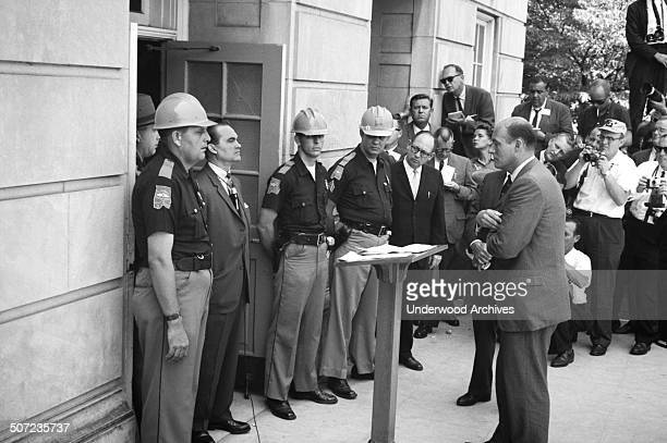 Governor George Wallace attempting to block integration at the University of Alabama stands in the door of Foster Auditorium while being confronted...