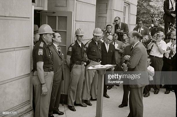 Governor George Wallace attempting to block integration at the University of Alabama Gov Wallace standing defiantly at a door while being confronted...