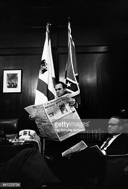 Governor George Wallace reads a newspaper in his office with one of his advisers On that day high schools in Alabama cities were integrated by...