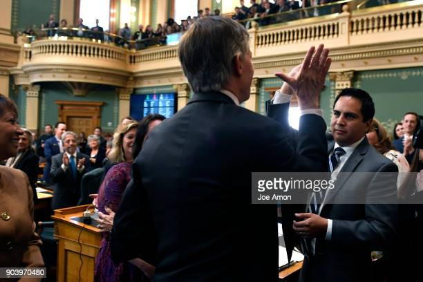 Governor John Hickenlooper hi 5's State Representative Dan Pabon after delivering his last Colorado State of the State address at the Colorado State...