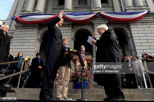 Governor John Hickenlooper with his son Teddy by his side takes the oath of office for his second term as governor from Colorado chief justice Nancy...