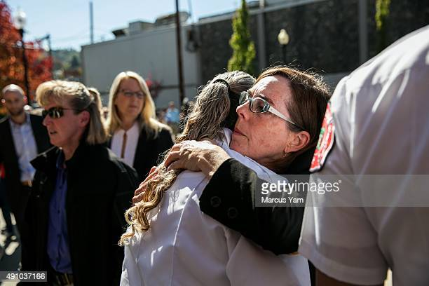 Governor Kate Brown hugs Douglas County Fire District Battalion Chief Teresa Mutschler after a press conference outside the Roseburg Fire Department...