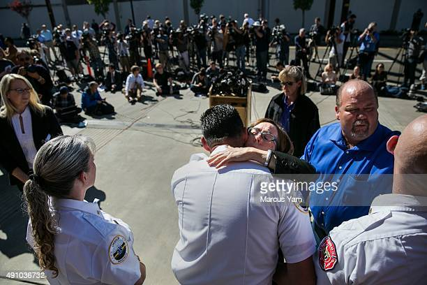 Governor Kate Brown hugs first responders gathered behind her after a press conference outside the Roseburg Fire Department Administration building...