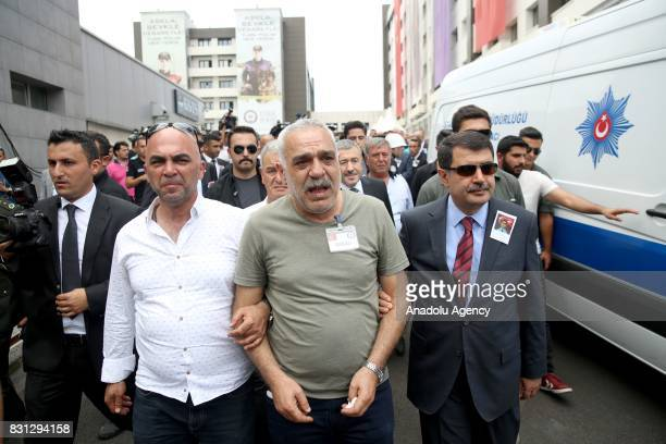 Governor of Istanbul Vasip Sahin holds Erdem Acar's arm father of police officer Sinan Acar who martyred by a Daesh suspect with a knife while a...