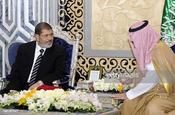 Governor of Jeddah Prince Mishaal bin Majed bin Abdul Aziz speaks with Egyptian President Mohamed Morsi as he arrives for the extraordinary summit in...