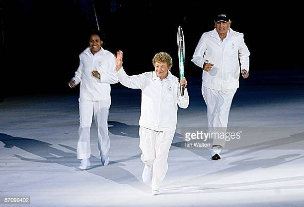 Governor of South Australia Marjorie JacksonNelson is followed by Ron Clarke Mayor of the Gold Coast and Cathy Freeman as she carries the Queen's...