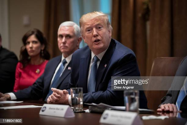 Governor of South Dakota Kristi Noem and U.S. Vice President Mike Pence listen as U.S. President Donald Trump speaks during a meeting about the...