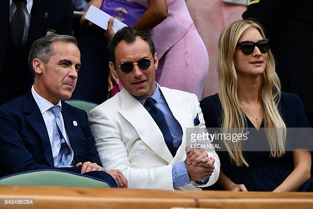 Governor of the Bank of England Mark Carney British actor Jude Law and partner Phillipa Coan sit in the royal box on centre court before the men's...