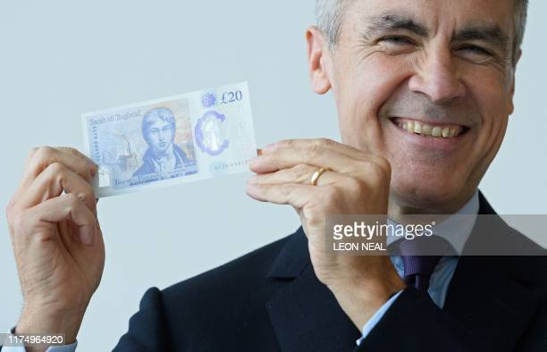 Governor of the Bank of England, Mark Carney poses for a photograph with the new twenty pound note featuring late British painter JMW Turner, during...
