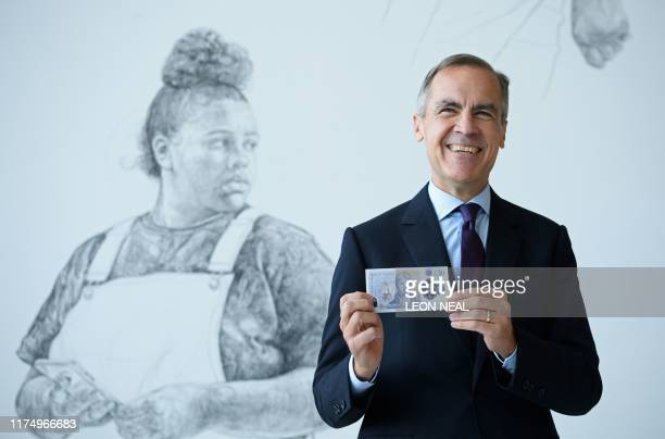 Governor of the Bank of England, Mark Carney poses for a photograph with the new twenty pound notefeaturing late British painter JMW Turner, during...
