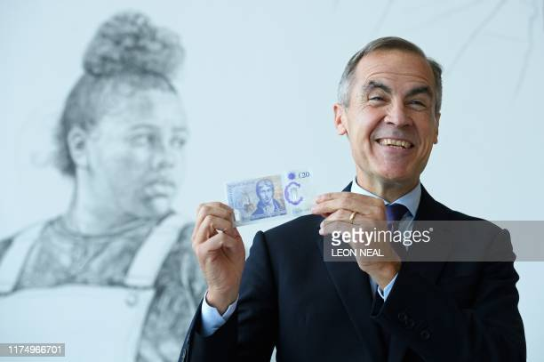 Governor of the Bank of England Mark Carney poses for a photograph with the new twenty pound notefeaturing late British painter JMW Turner during the...