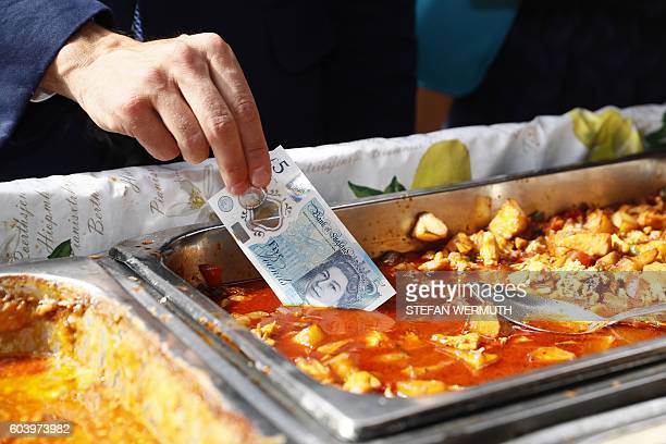 TOPSHOT Governor of the Bank of England Mark Carney tests a new polymer five pound note by dipping it in a tray of food as he buys lunch at...
