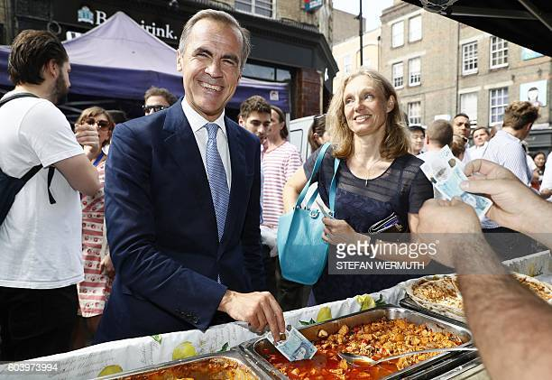 Governor of the Bank of England Mark Carney tests a new polymer five pound note by dipping it in a tray of food as he buys lunch at Whitecross Street...