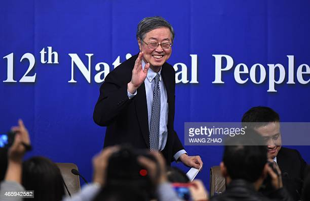 Governor of the People's Bank of China Zhou Xiaochuan waves as he leaves after a press conference during the third session of the12th National...