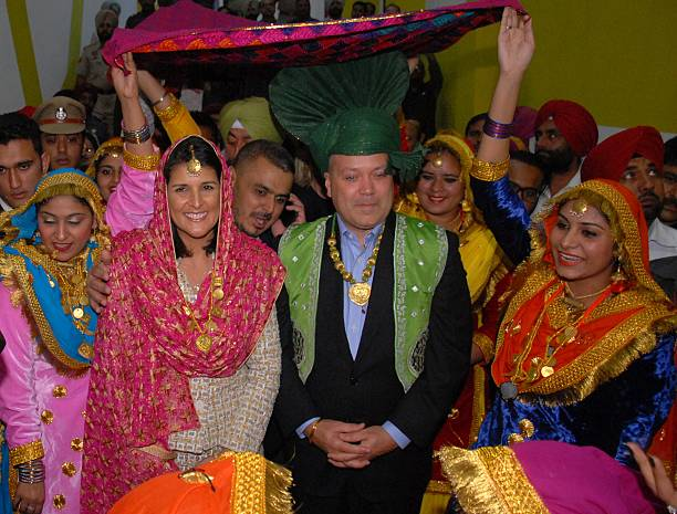 Governor of the US State of South Carolina Nikki Haley poses with her husband Michael Haley and traditional Punjabi dancers as she arrives to attend..