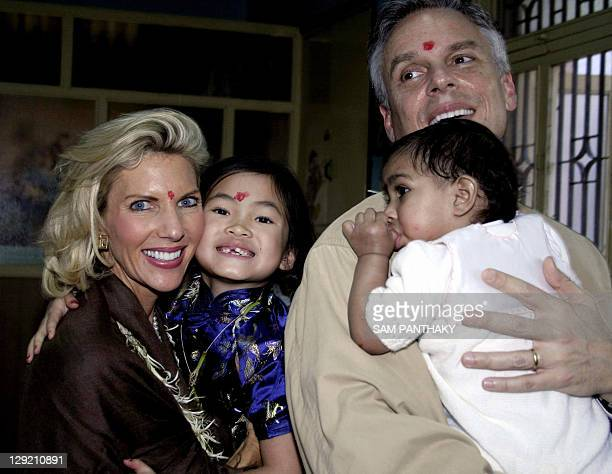 Governor of the US State of Utah Jon M Huntsman Jnr holds Indian child Asha Bharati as his wife Mary Kaye Huntsman and their adopted Chinese child...