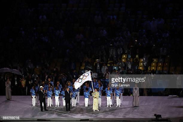 Governor of Tokyo Yuriko Koike waves the IOC flag while IOC President Thomas Bach and the Mayor of Rio de Janeiro Eduardo Paes watch on stage at the...