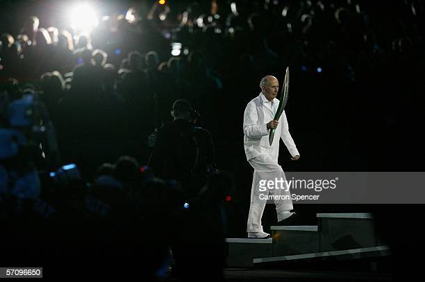 Governor of Victoria John Landy carries the Queen's Baton during the Opening Ceremony for the Melbourne 2006 Commonwealth Games at the Melbourne...