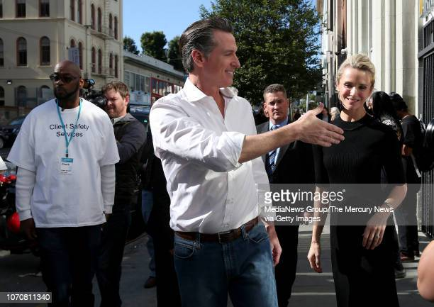 Governorelect Gavin Newsom and his wife Jennifer right greet people as they walk through the Tenderloin District of San Francisco Calif on Thursday...